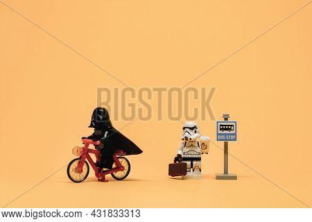 Darth Vader On Bicycle Passing Public Bus Stop. Public Transport Concept. Illustrative Editorial. Se