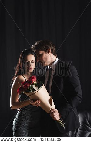 Young Man In Suit Holding Bouquet Of Red Roses Near Girlfriend In Elegant Dress On Black