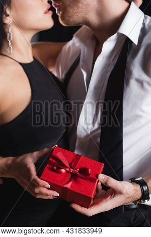 Partial View Of Man Holding Gift Box And Kissing With Woman In Dress