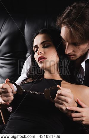 Dominant Man Holding Handcuffs Near Seductive Young Girlfriend On Black