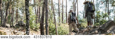 Multiethnic Couple With Backpacks Walking On Stones In Forest, Banner.