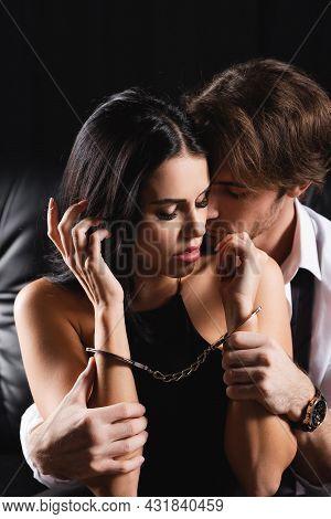 Dominant Man Hugging Handcuffed Girlfriend On Black