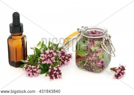 Oregano herb flowers leaves steeped in oil with essential oil bottle. Natural herbal plant medicine. Can ease IBS symptoms, is anti bacterial, anti inflammatory, anti viral, is an anti coagulant.
