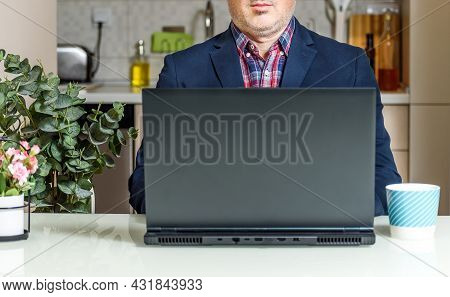 Trendy Mature Man Working From Home With Laptop Sitting At The Table In His Kitchen, Dressed In Suit