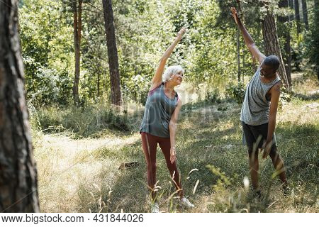 Elderly Multiethnic Couple Warming Up In Forest.