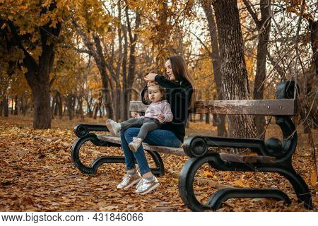 Young Female Woman Babysitter And Toddler Baby Girl Walk In Autumn Park. Happy Family Mom And Toddle