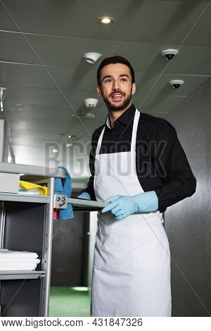 Smiling And Bearded Housekeeper In Rubber Gloves Standing Near Cart In Corridor Of Hotel