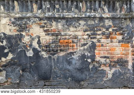 Old Brick Wall With Remnants Of Time-damaged Plaster. Old City Background And Texture