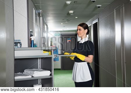 Young Maid Holding Handle Of Housekeeping Cart