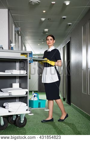 Full Length Of Young Chambermaid In Apron Holding Handle Of Housekeeping Cart