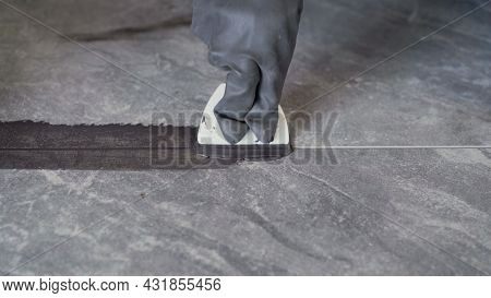 Grouting Ceramic Tiles. Tilers Filling The Space Between Tiles Using A Rubber Trowel. Grouting After