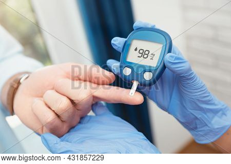 Doctor Making Blood Sugar Test In Clinic For Diabetes. Treatment Of Diabetes Concept.