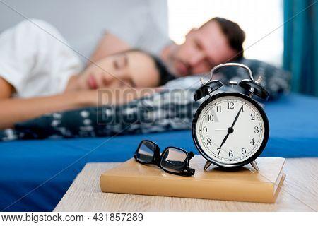 Couple Sleeping In Bed. Alarm Clock On The Nightstand. Healthy Sleep Concept