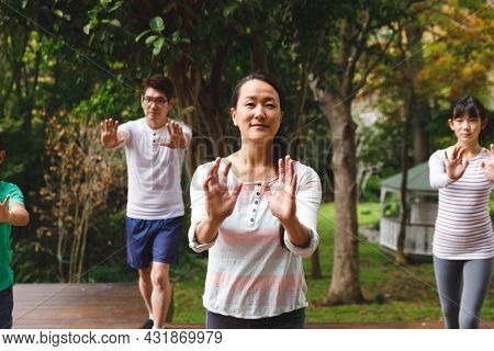 Happy asian parents, son and daughter exercising outdoors, practicing tai chi. family fitness time in garden.