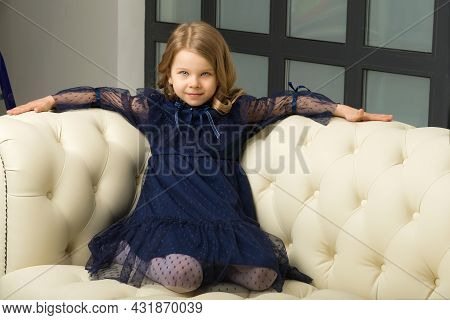 Lovely Little Girl Sitting On Her Knees On Couch. Portrait Of Cheerful Adorable Blonde Girl Wearing