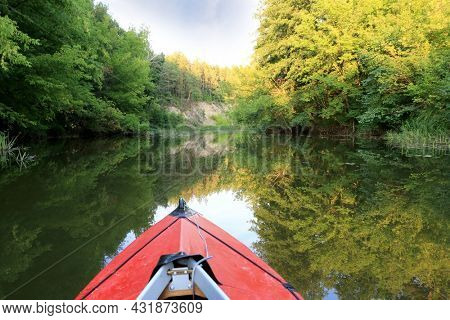 Red kayak in wild river in forest
