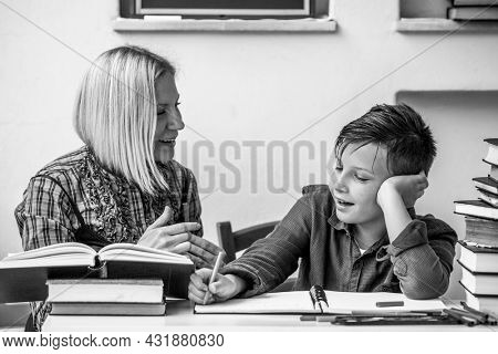 Elementary school student during homework with a tutor. Black and white photo.