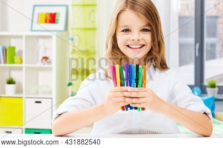 art, hobby and school concept - happy smiling student girl showing colorful felt-tip pens over home background