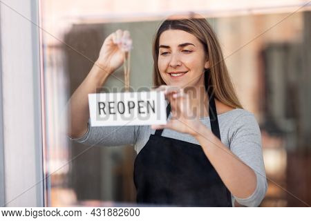 small business, reopening and service concept - happy smiling woman hanging reopen banner to window or door glass