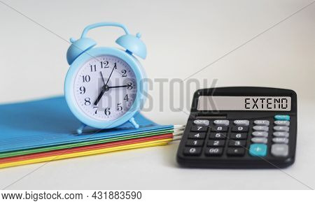 Extend Word Written On A Calculator Display And On A White Background With A Clock And Folders