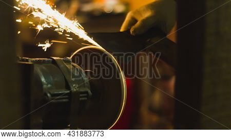 Sharpen The Knife On The Abrasive Wheel, Sparks Fly From Grinding Metal.