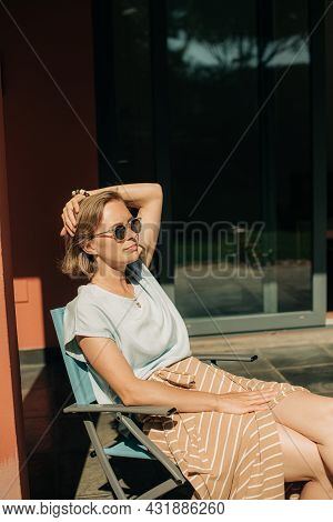 Calm Mid Adult Woman Sunbathing In Chair Outdoors. Lady Wearing Sunglasses Resting On Terrace At Her