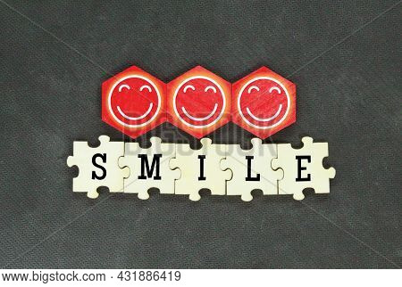 Wooden Puzzle And Hexagon With Smile Icon The Word Smile