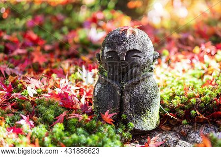Japanese Jizo Sculpture Doll With Falling Red Maple Leaf In Japanese Garden At Enkoji Temple, Kyoto,