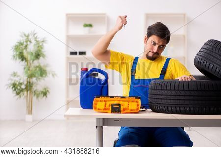 Young male garage worker with tyre at workshop