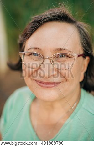 Portrait Of Smiling Mature Woman In Eyeglasses. Close-up Of Smiling Female Face Looking At Camera Ou