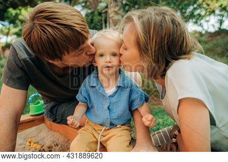 Portrait Of Happy Parents Kissing Child In Sandpit. Cute Little Girl Sitting In Sandbox With Her Lov