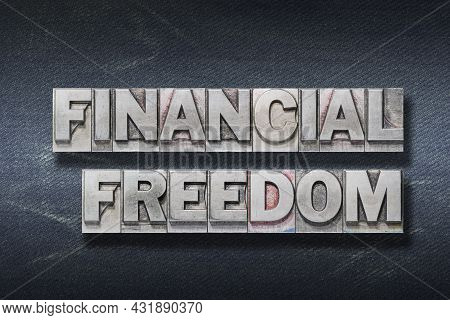 Financial Freedom Phrase Made From Metallic Letterpress On Dark Jeans Background