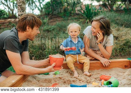 Happy Family With Toddler Child Playing In Sandbox. Toddler Girl And Her Mother Sitting At Sandpit A
