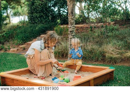 Happy Mother Playing With Child In Sandbox. Mid Adult Woman Walking With Her Little Daughter Outdoor