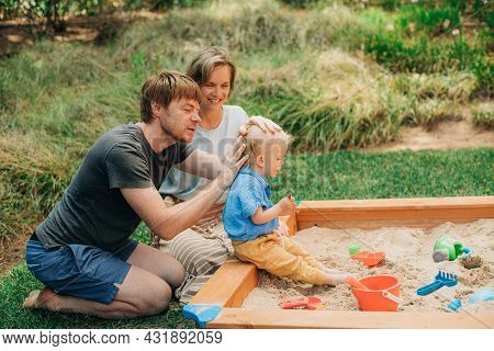 Portrait Of Happy Family Playing In Sandbox. Toddler Girl Sitting In Sandbox And Her Father Patting