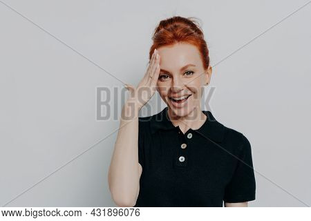 Portrait Of Pretty Redhaired Woman With Hair In Bun Dressed In Black T-shirt Polo Forgetting Somethi