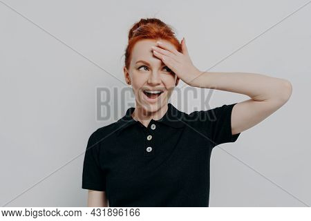 Happy Young Redhead Woman With Opened Mouth Touching Her Forehead With Hand, Smiling And Looking Asi