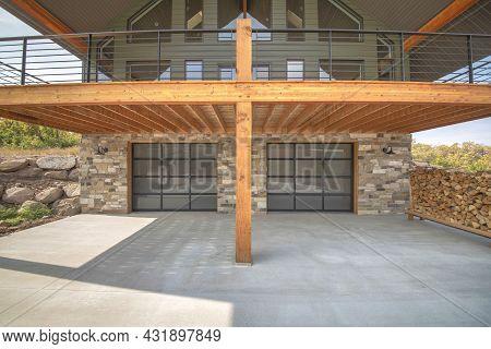 Two Glass Garage Door Of A Modern Custom House With Stone Veneer Siding