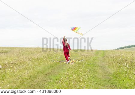 A Child Running With A Kite On The Background Of Grass And Sky. A Child With A Kite
