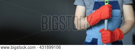 Hands Of Cleaner In Yellow Gloves Holding Mop Handle