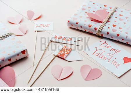 Decorations And Gifts For Valentines Day On A Pink Surface. Props And Wrapped Gift Boxes.