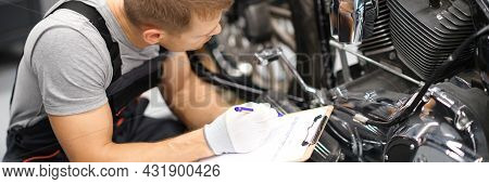 Foreman In Service Repair Center Diagnoses Parts On Motorcycle