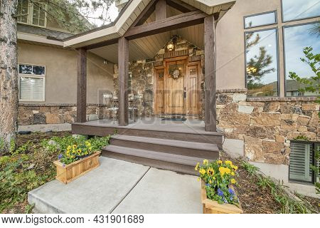 Porch Of A House With Huge Single Wooden Door With Wreath And Lockbox