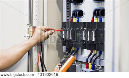 Engineers Working To Inspect And Maintain Electrical Control Cabinets.