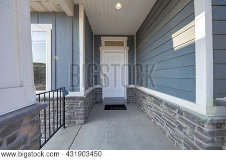 Entrance Of A House With White Front Door And Transom Window With Black Doormat