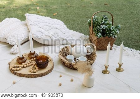 White Blanket At Green Grass, Outdoor Decor For Picnic. Pillows, Dishes, Wooden Decoration At Summer