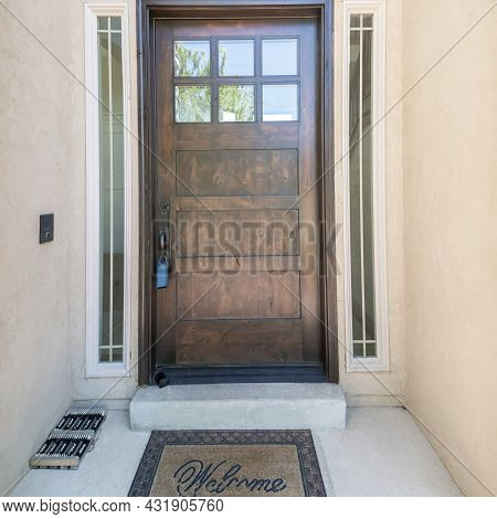 Square Frame Exterior Of A Front Door With Glass Panels And Doormat
