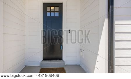 Pano Exterior Of A House With A View Of Black Wooden Door With Glass Panel And An Enginered Wood Sid