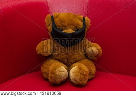 A Brown Teddy Bear Sits On The Couch Wearing A Medical Mask. Concept: Diseases Among Children, Infan