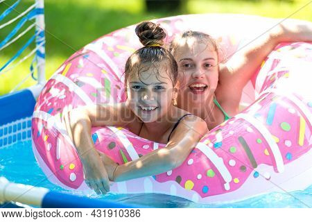 The Perfect Way To Stay Cool. Happy Kids Swim In Donut Pool Float. Pool Games. Poolside Play. Summer